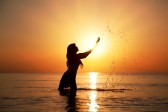 13125722-silhouette-of-woman-making-splashes-in-the-rays-of-the-rising-sun-horizontal-photo